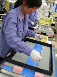 接下来,工作人员安装前边框,并在放入液晶面板之前贴上缓冲材料。